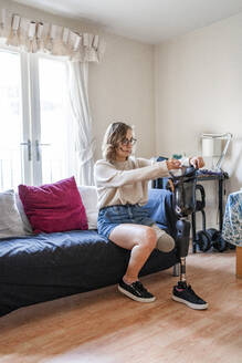 Young woman with leg prosthesis sitting on couch at home - FBAF01289