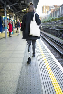 Rear view of young woman with leg prosthesis walking at station platfom - FBAF01298
