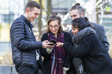 Happy friends looking at smartphone in the city - FBAF01304