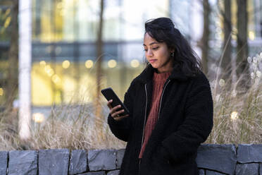 Young woman using cell phone in the city - FBAF01307