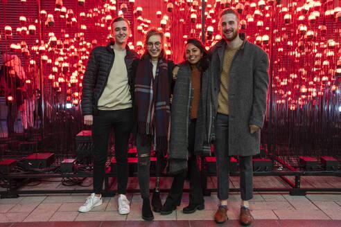 Portrait of happy friends in front of red light bulbs - FBAF01313