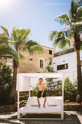 Full length of boy dancing on lounge chair against palm trees in resort - MASF16775