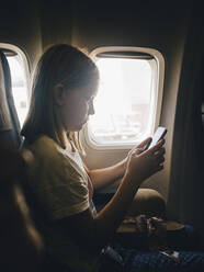 Side view of girl using mobile phone while sitting by airplane window - MASF16793