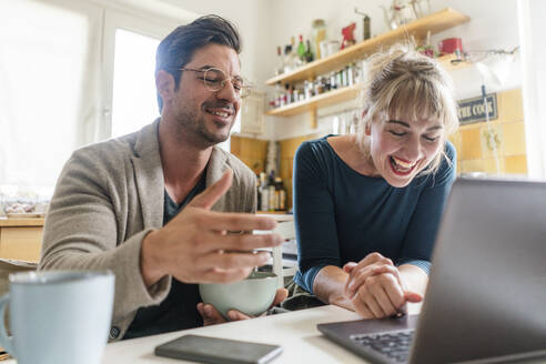 Happy couple sitting at table in kitchen using laptop - KNSF07649