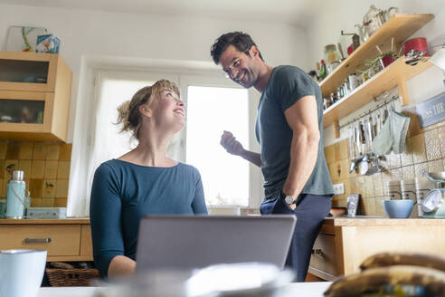 Happy couple in kitchen with laptop - KNSF07658