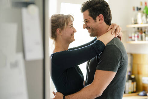 Happy couple embracing in kitchen at home - KNSF07670