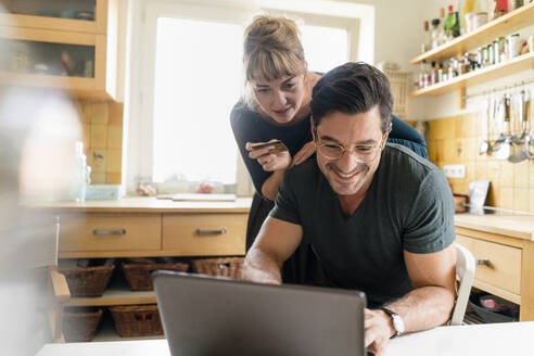 Happy couple shopping online in kitchen at home - KNSF07673