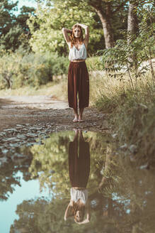 Red-haired woman posing in front of a puddle, mirrored - MTBF00355