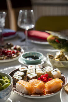 Spain,Plate of ready-to-eat sushi on set dining table - AFVF05462