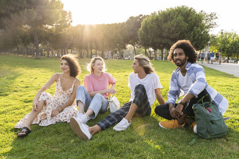 Group of friends relaxing on a meadow in park - AFVF05473