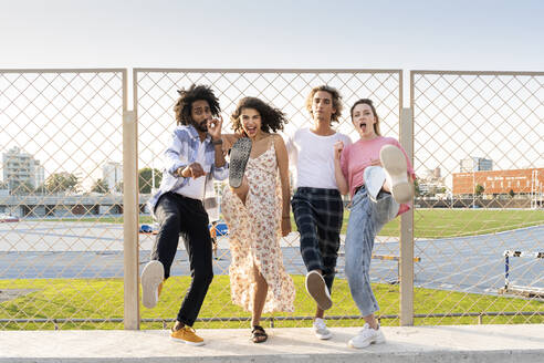 Portrait of happy friends posing at a wire mesh fence - AFVF05485