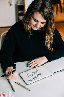 Stock photo of a lettering artist at work with her sketch book. - CAVF76022