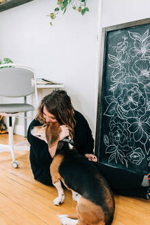 Stock photo of a lettering artist in her studio with her dog. - CAVF76028