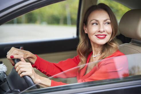 Portrait of smiling mature woman driving car - PNEF02471