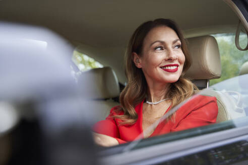 Portrait of happy mature woman in car - PNEF02474