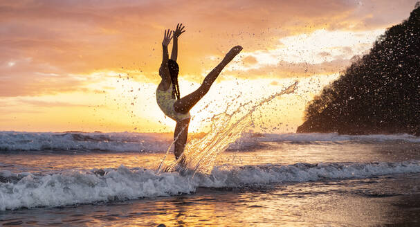 Teenage girl practicing gymnastic at seafront by sunset, Jaco Beach, Costa Rica - AMUF00012