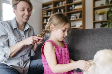 Mother braiding her daughter's hair on the couch - VYF00002