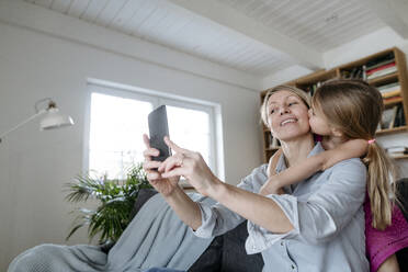 Mother and little daughter taking selfie with smartphone at home - VYF00008