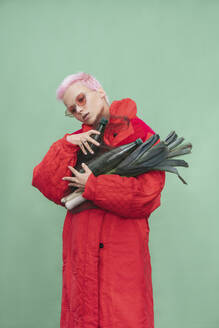 Portrait of young woman with short pink hair wearing red coat - VPIF02103