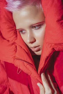 Portrait of young woman with short pink hair wearing red jacket in front of red background - VPIF02121