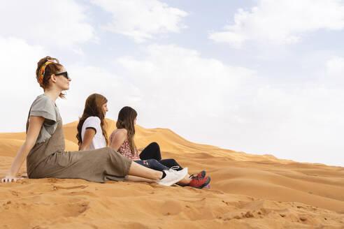 Three young women sitting in sand dune in Sahara Desert, Merzouga, Morocco - AFVF05527