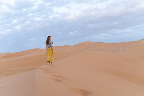 Young woman on sand dune in Sahara Desert, Merzouga, Morocco - AFVF05533