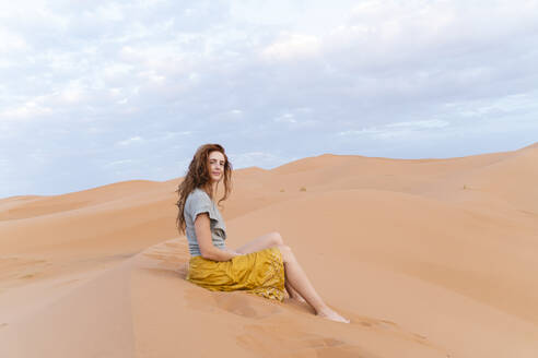 Portrait of redheaded young woman sitting in sand dune in Sahara Desert, Merzouga, Morocco - AFVF05536