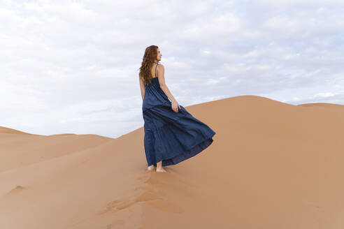 Young woman standing on sand dune in Sahara Desert, Merzouga, Morocco - AFVF05545