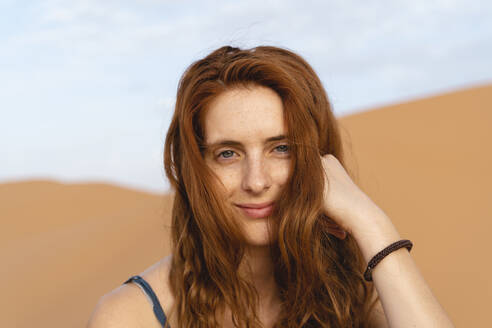 Portrait of smiling redheaded young woman in Sahara Desert, Merzouga, Morocco - AFVF05551