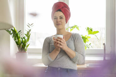 Portrait of woman with head wrapped in a towel drinking a coffee - MOEF02849