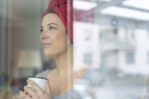 Portrait of woman with head wrapped in a towel drinking a coffee behind windowpane - MOEF02852
