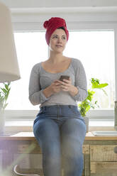 Smiling woman with head wrapped in a towel holding smartphone - MOEF02855