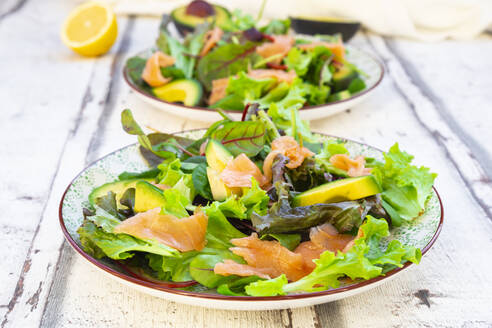 Two plates of ready-to-eat green salad with arugula,LolloRossolettuce, baby spinach, beetroot leaves, avocado, corn salad and salmon - LVF08641