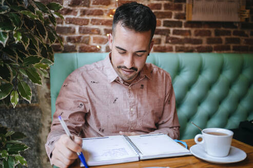 Man in a cafe taking notes - KIJF02927