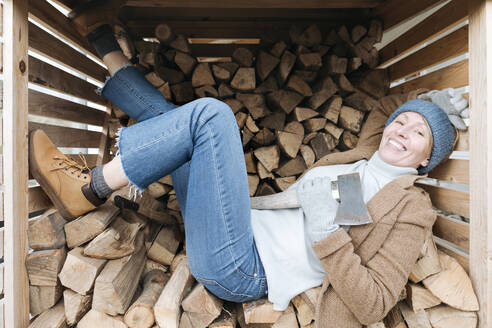 Portrait of happy mature woman with axe lying on firewood - VYF00012