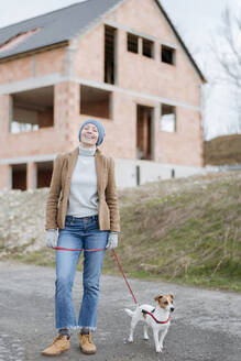 Portrait of happy mature woman going walkies with her dog - VYF00021
