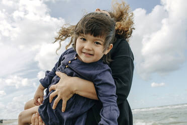 Portrait of happy little girl on her mother's arms - OGF00164