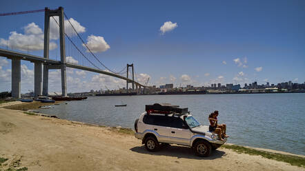 Mozambique, Katembe, Adult couple sitting on hood of 4x4 car admiring view of Maputo Bay with city and Maputo-Katembe Bridge in background - VEGF01643