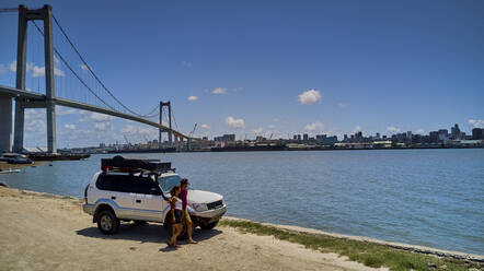 Mozambique, Katembe, Adult couple standing by 4x4 car admiring view of Maputo Bay with city and Maputo-Katembe Bridge in background - VEGF01646