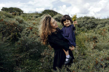 Happy mother and little daughter with picked flowers in nature, The Hague, Netherlands - OGF00183