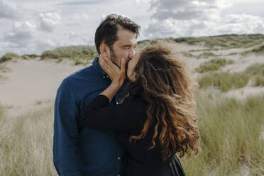 Woman kissing her husband in the dunes, The Hague, Netherlands - OGF00189