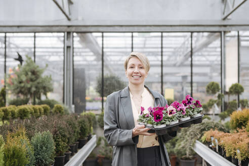 Smiling woman with pansies in flower shop - VYF00023