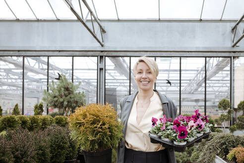 Smiling woman with pansies in flower shop - VYF00026