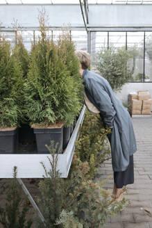 Woman hiding her head in plants in flower shop - VYF00041