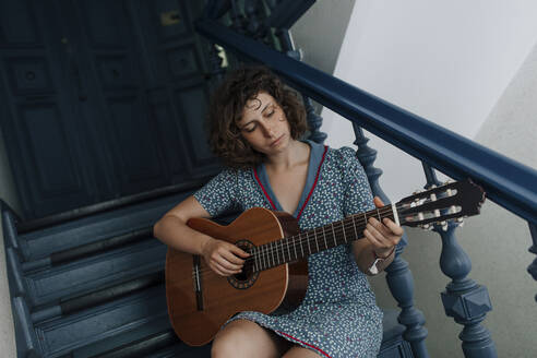 Portrait of young woman sitting on stairs playing guitar - OGF00193