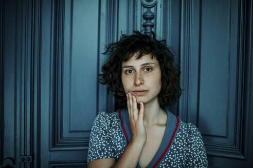 Portrait of young woman in front of blue wooden door - OGF00199