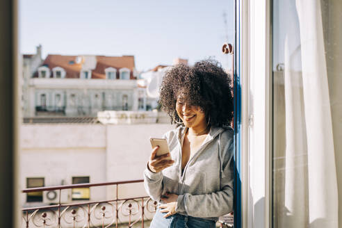 Portrait of happy young woman with curly hair holding cell phone on balcony - DCRF00084