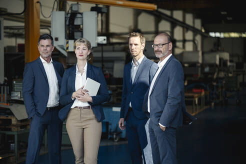 Confident business team standing in a factory - KNSF07688