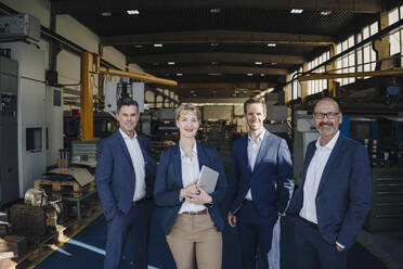 Portrait of confident business team standing in a factory - KNSF07700