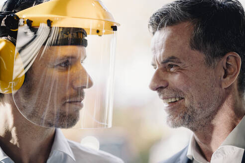 Smiling businessman and man wearing safety helmet facing each other - KNSF07730